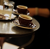 Two espresso cups and a glass of water on bistro table