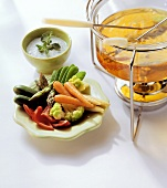 Fondue pot, raw vegetables on plate and herb dip