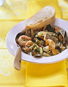 Fish soup with seafood on plate with bread and spoon