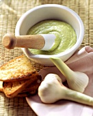 Garlic mayonnaise with avocado in mortar; toast