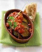 Aubergines in tomato sauce in baking dish; white bread