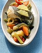 Oven-baked fish with lemon and vegetables on white plate