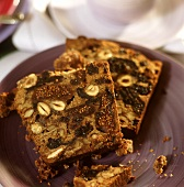 Two slices of fruit cake with nuts on a plate