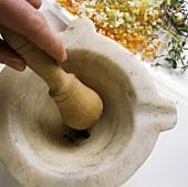 Crushing peppercorns in a mortar