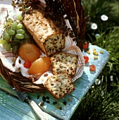 Cake with crystallised fruit in a basket on grass