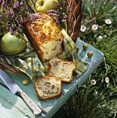 Olive and ham loaf, apples & herbs in basket in meadow