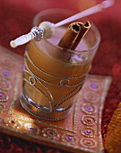 Indian spiced tea with cinnamon stick in glass
