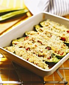 Courgette boats with herbs in baking dish