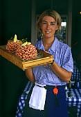 Swedish waitress holding tray of shrimps
