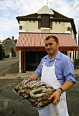 French butcher holding sausages on tray
