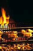 Ducks on spit in front of open fire