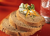 Three slices of buckwheat bread, one with herb quark