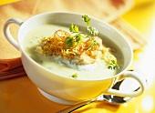 Cream of potato soup with sauerkraut, ham and herbs