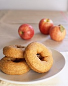 Apple doughnuts on plate in front of fresh apples