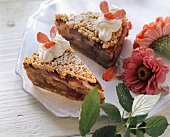 Plum and almond cake with cream and flower petals