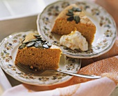 Two pieces of pumpkin cake with pumpkin seeds, one with cream