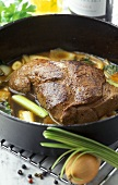 Roast venison with vegetables in stew pot