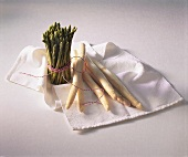 Bundle of green asparagus and white asparagus spears on cloth