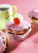 Cappuccino & cherry muffins with pink icing & cocktail cherry