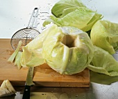 Preparing white cabbage: cutting out stalk, removing leaves