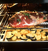 Roasting leg of lamb and vegetables in the oven