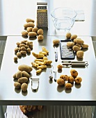Various types of potatoes and kitchen utensils