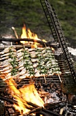 Frog's legs on skewers above open fire