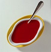 Tomato sauce in sauce boat with spoon