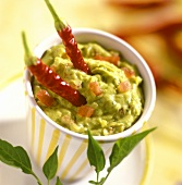 Avocado dip with diced tomatoes and chili peppers