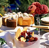 Almond cake and fresh fruit on table in open air
