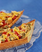 Toasted baguette pieces with chicken and tomatoes