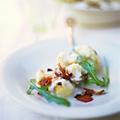 Cauliflower in cream sauce with fried bacon and rocket