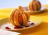 Stuffed apples in puff pastry with cherry sauce