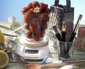 Strawberries on scales surrounded by kitchen utensils