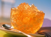 Orange jelly with strips of rind in glass bowl