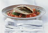 Provencal trout with tomato ragout on plate; cutlery
