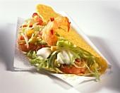Taco with shrimp salad on paper napkin
