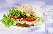 Filled roll with tomatoes, cheese and lettuce leaf
