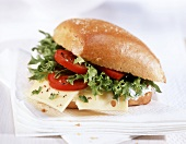 Filled roll with cheese, tomatoes & lettuces leaves
