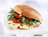 Belegtes Brötchen mit Käse, Tomaten und Salatblättern