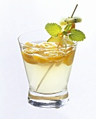 Kumquat punch with skewered exotic fruit in glass