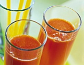 Two red pepper drinks in front of glass with yellow straws