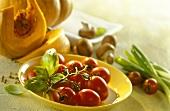 Still life with vine tomatoes, pumpkin, mushrooms and basil