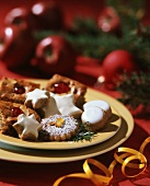 Assorted Christmas biscuits on plate; yellow bow