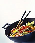 Vegetables with strips of turkey in wok; chopsticks