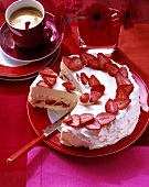 Meringue gateau with strawberries, piece cut; coffee