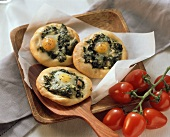 Small spinach pizzas with egg;  tomatoes on the vine
