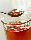 Apple jelly in jar and on spoon