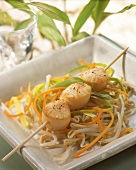 Scallop kebab on julienne vegetables and sprouts