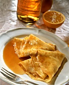 Crepes suzettes with orange sauce on plate
